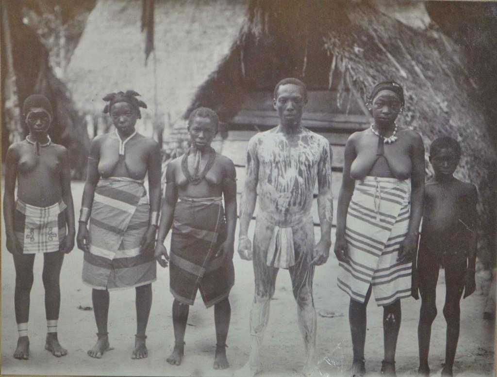 """Bijgaande foto, door de houtvester Gonggrijp geschoten op 6 november 1918, geeft als bijschrift o.a.: """"Toboi met pimba ingesmeerd, zoekt winti. De pimba op het voorhoofd van de vrouwen is afkomstig van het dansfeest van de vorige avond."""""""